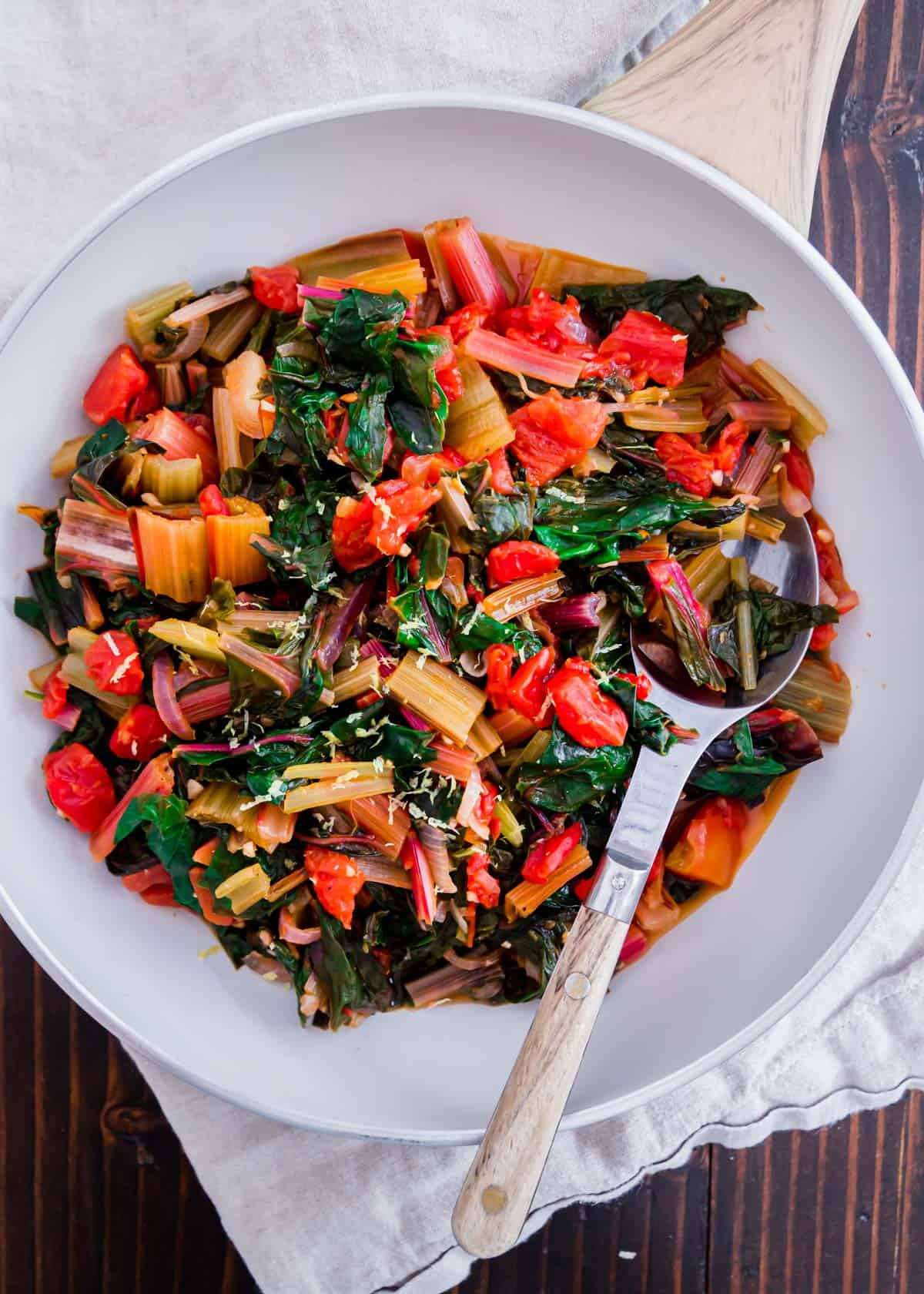 A simple recipe for sautéed Swiss chard with garlic, onions, tomatoes and lemon. Garnished with some optional fresh parmesan cheese and easily made in a pot or skillet. It's a low-calorie, vegetarian healthy side dish packed with all the nutrients from fresh leafy greens.
