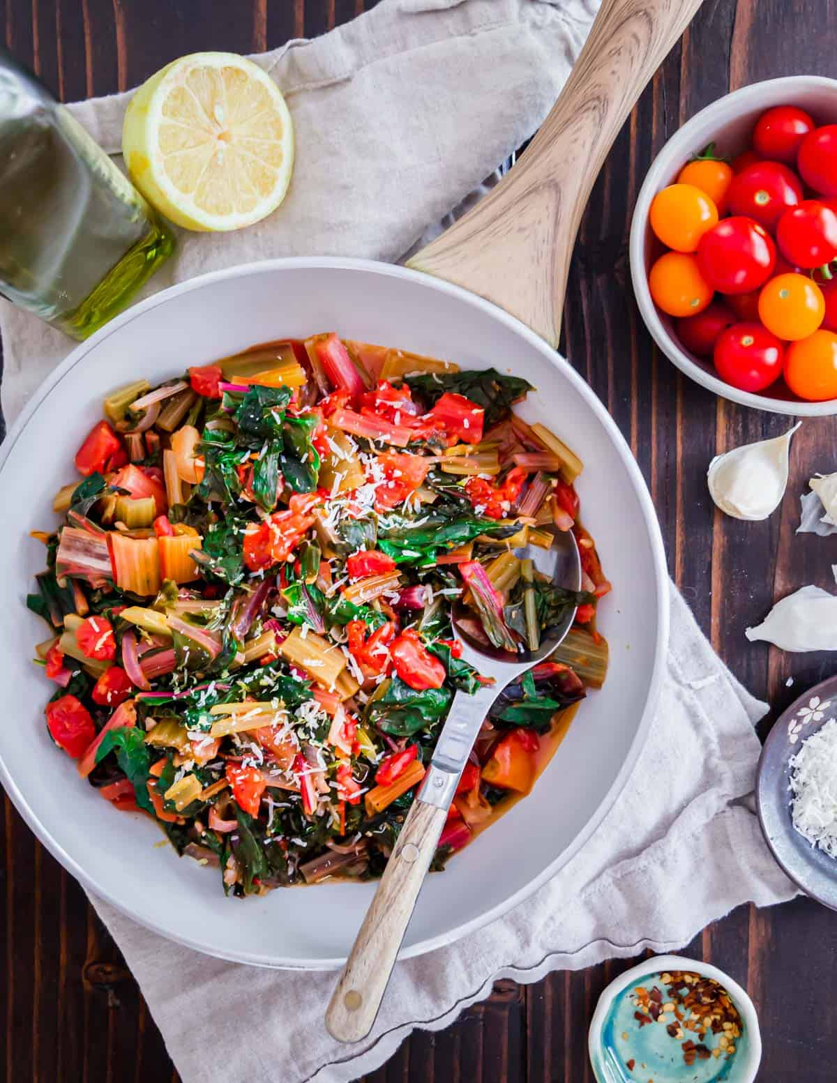 Easy sautéed Swiss chard with tomatoes, onions, garlic and lemon make a delicious and healthy vegetable side dish for summer.