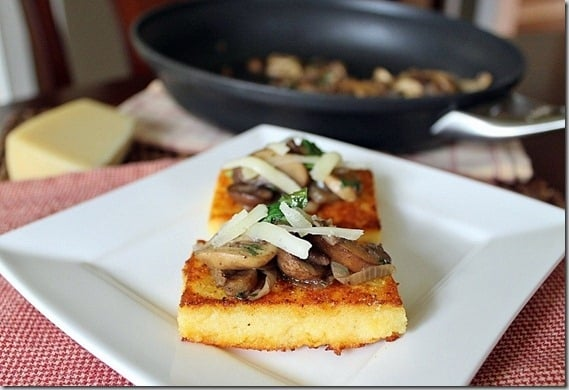 Crispy pan-fried cornmeal cakes topped with mushroom ragu and gruyere are a delicious bite for a party appetizer.