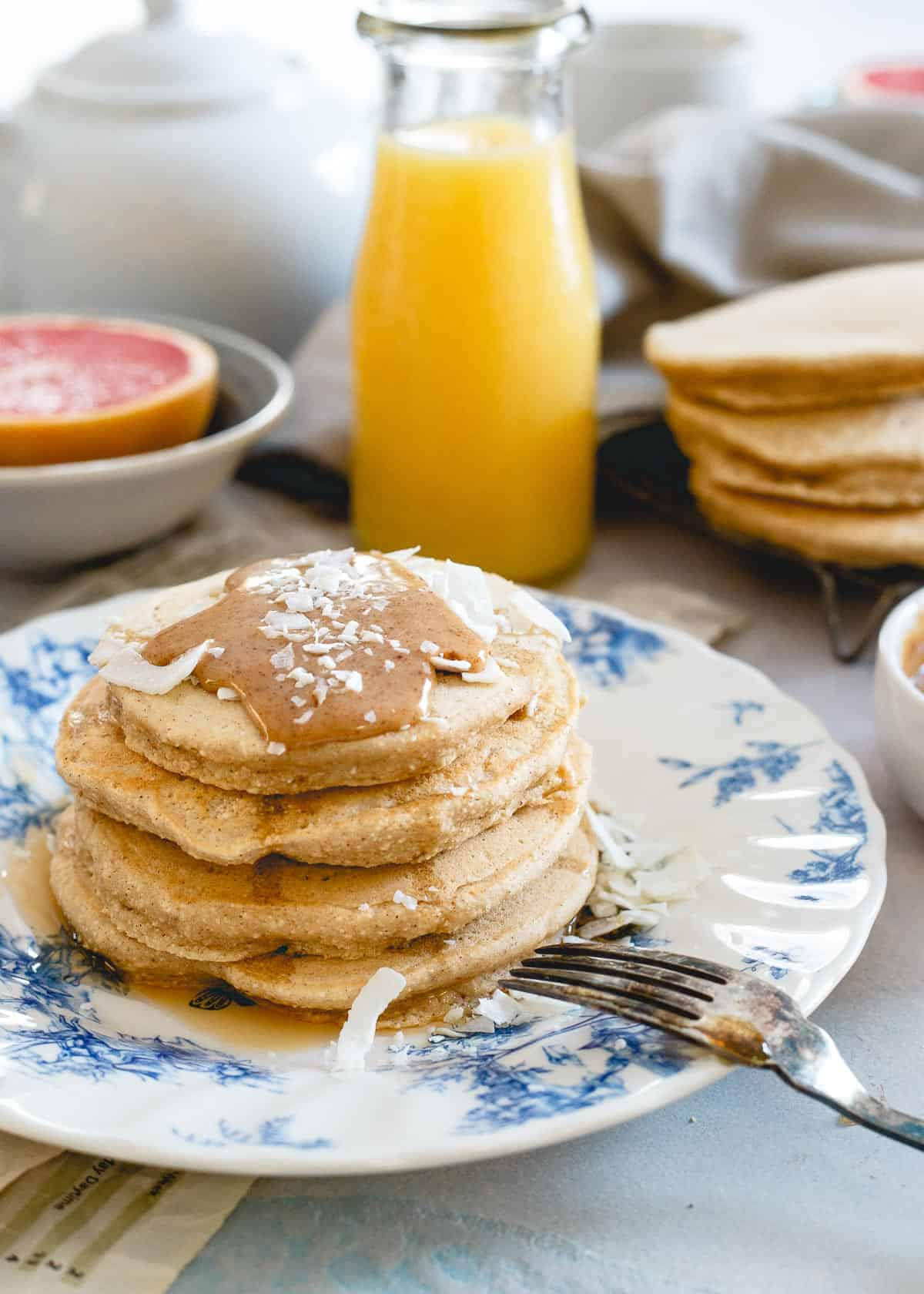 Doughy coconut flour pancakes with a coconut almond butter sauce are a simply delicious way to enjoy a pancake breakfast.