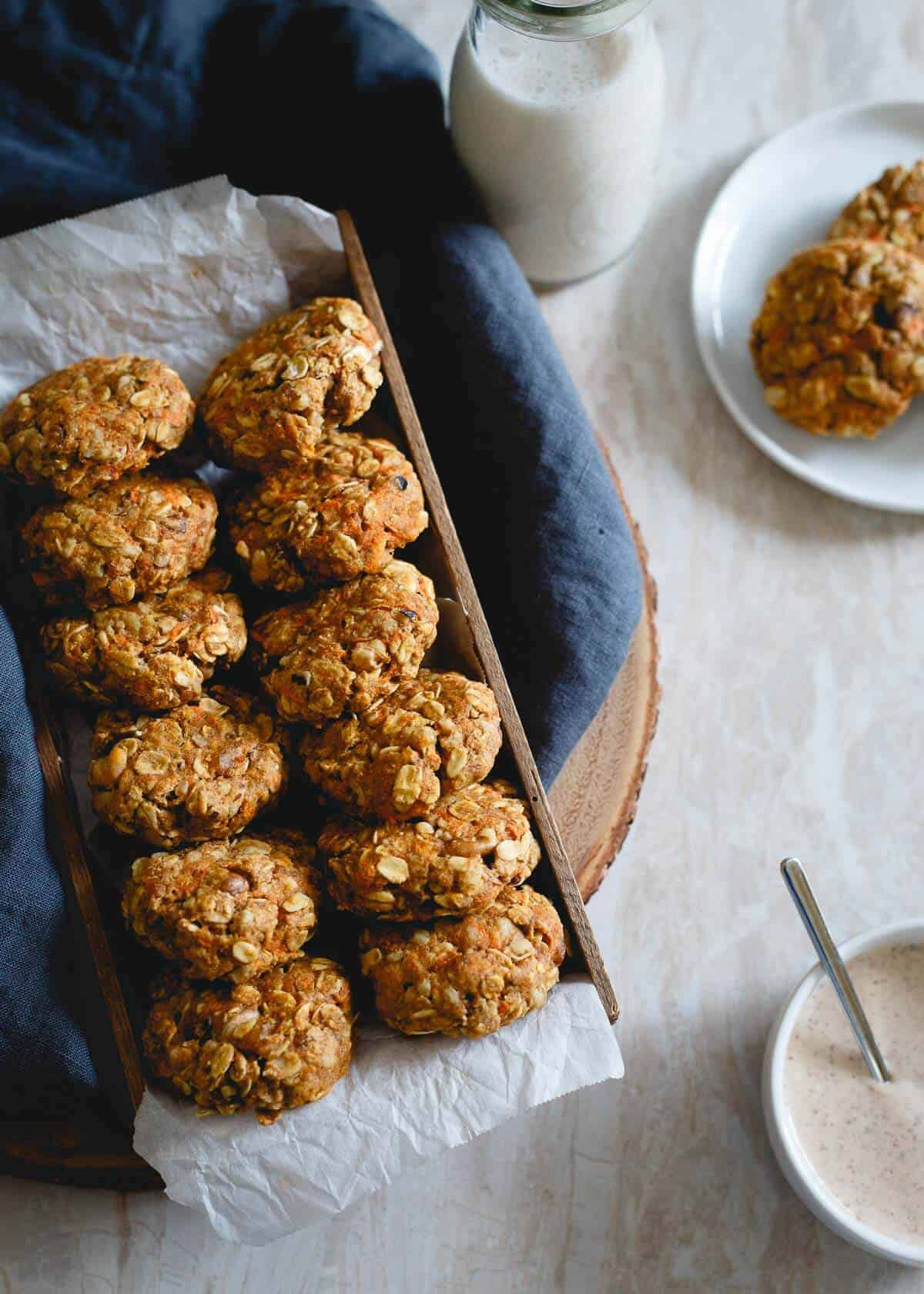 These healthy carrot cake cookies made with oats and whole wheat flour are packed with raisins, walnuts, lemon zest and ginger. Drizzle them with the optional almond butter cream cheese topping for a true creamy carrot cake like bite. No added sugar, no butter, still completely delicious and guilt-free.