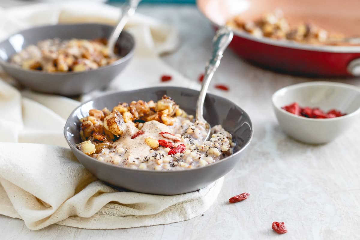 Warm quinoa cereal is topped with almond butter, caramelized banana walnut compote and some goji berries for a healthy and satisfying breakfast.