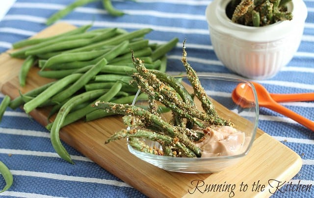 These baked green bean fries are served with a spicy yogurt dipping sauce for a crispy and healthy side dish or snack you can feel good about eating.