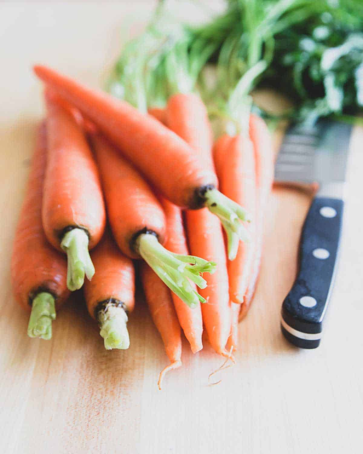 Tender spring carrots with greens become candied with brown sugar and butter on the stovetop.