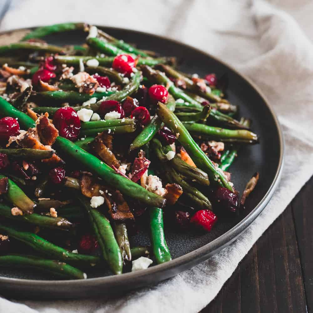Slightly crunchy green beans, burst cranberries, salty bacon and goat cheese crumbles make a stunning and delicious side dish for any holiday dinner.