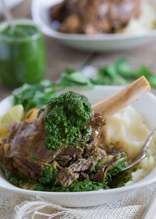 These citrus braised lamb shanks are served with a spicy green harissa.