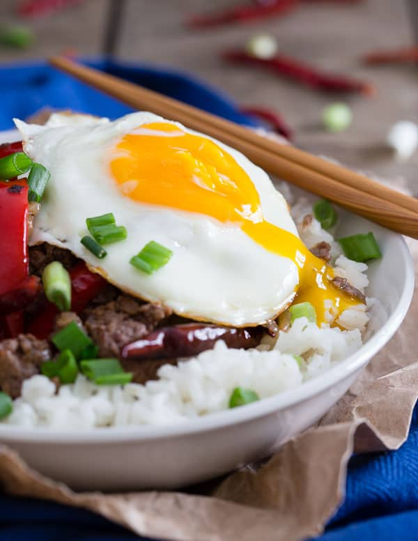 This spicy beef and red pepper rice bowl is cooked with dried red chili peppers and topped with a runny egg.