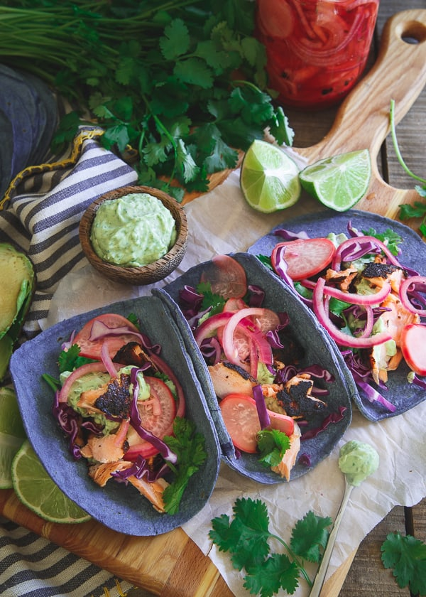 These blackened salmon tacos are topped with quick pickled radishes and red onion, an avocado cilantro cream and served on blue corn tortillas for one amazing bite!