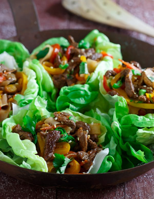 Sticky sweet Korean style steak is tossed with peppers, carrots, green onions, rice noodles and served in crispy lettuce cups.