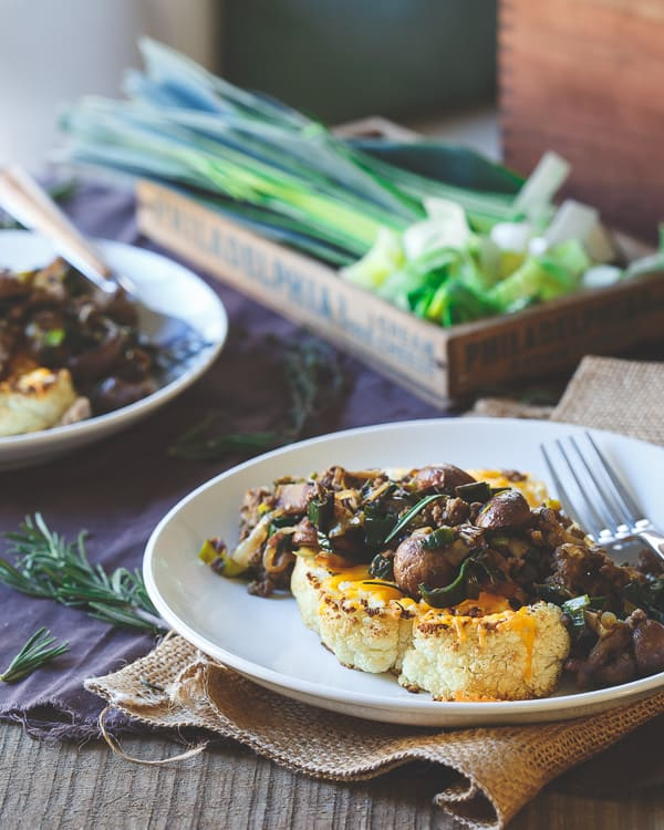 Thick cut and hearty cauliflower steaks are topped with melted cheddar and a savory bison, crimini mushroom and leek saute. It's healthy comfort food heaven.