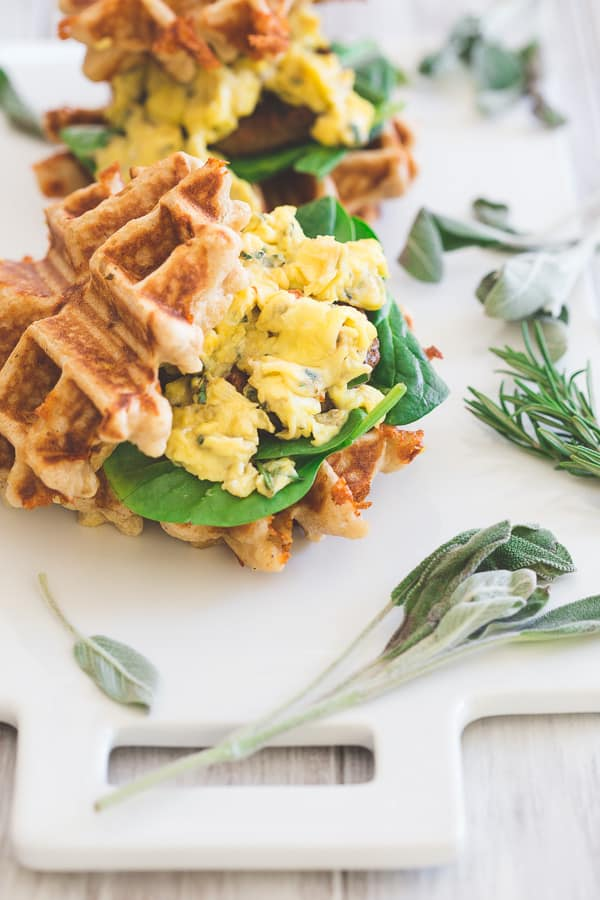 These mini sausage and egg waffle sandwiches are the perfect breakfast or even brinner! Fresh greens, melted cheddar, herbed scrambled eggs and Jones sausage make the perfect bite.