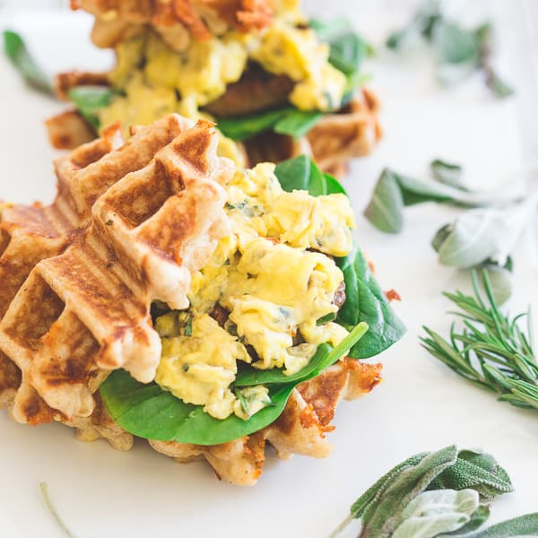 Mini sausage and egg waffle sandwiches are the perfect breakfast or even brinner! Fresh greens, melted cheddar, herbed scrambled eggs and Jones sausage make the perfect bite.