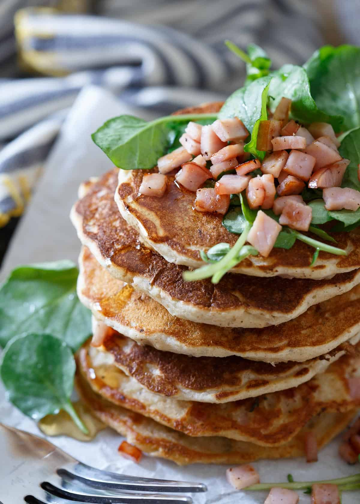 Savory Canadian Bacon Pancakes make the perfect breakfast for dinner meal. Stuffed full of savory ingredients and topped with a simple refreshing watercress salad.