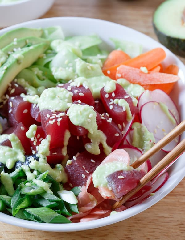 A quick and easy tuna sushi bowl packed with radishes, carrots, cucumber, seaweed and avocado then drizzled in a spicy avocado wasabi dressing.