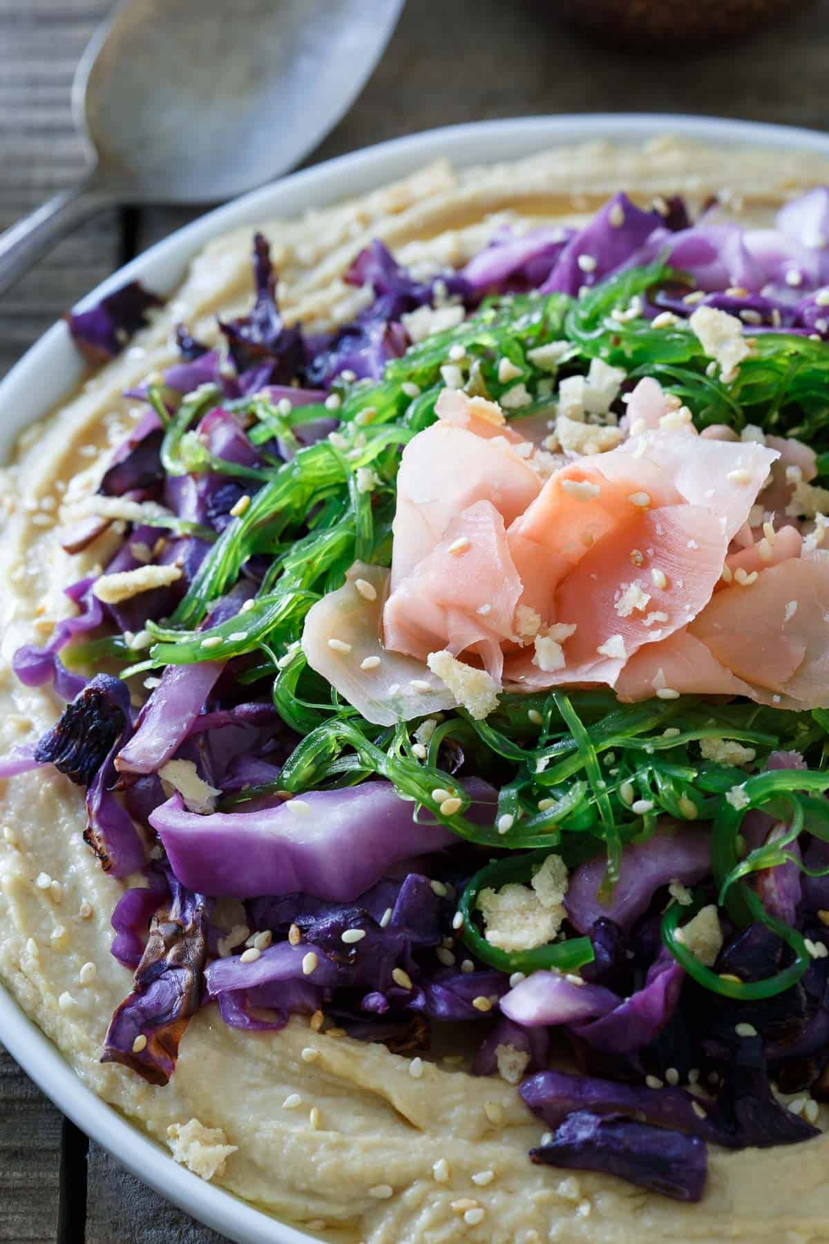 Sesame cabbage, seaweed salad and pickled ginger are piled high in this Asian hummus platter.