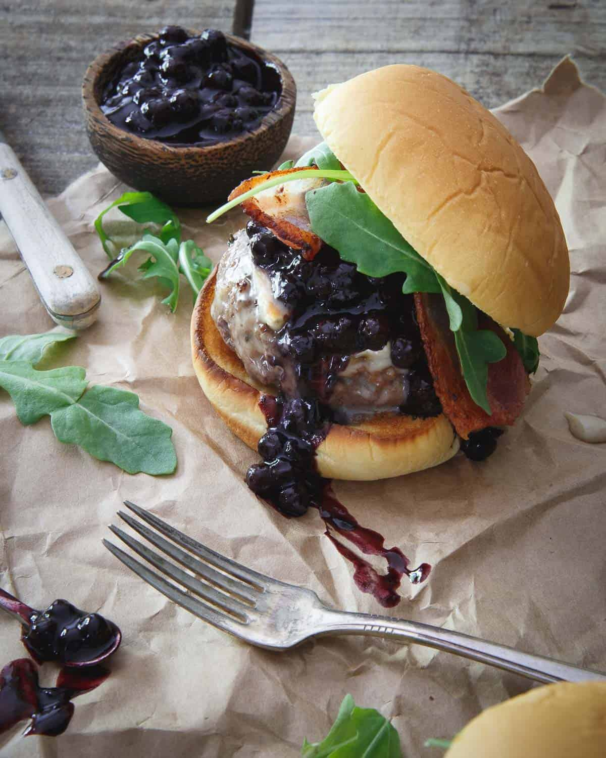 Sweet and tangy blueberry BBQ sauce gets slathered on this brie burger with crispy bacon and arugula.