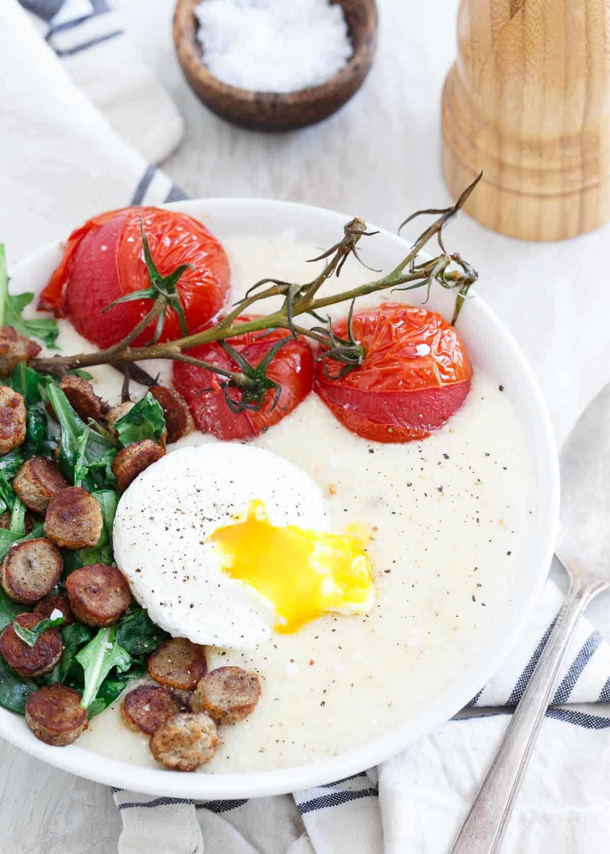 These cheddar cheese grits are topped with a chicken sausage baby greens sauté, oven burst vine ripe tomatoes and a perfectly poached runny egg.
