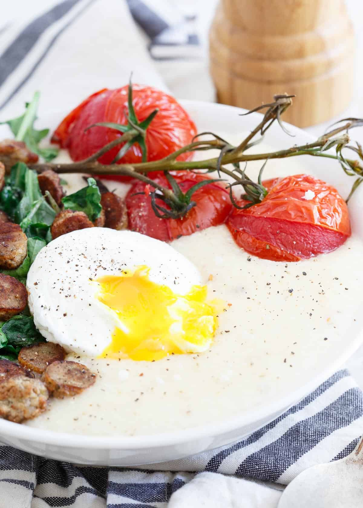 Chicken Sausage Cheese Grits with Burst Tomatoes and a runny poached egg are an easy brinner option for hectic weeknights.