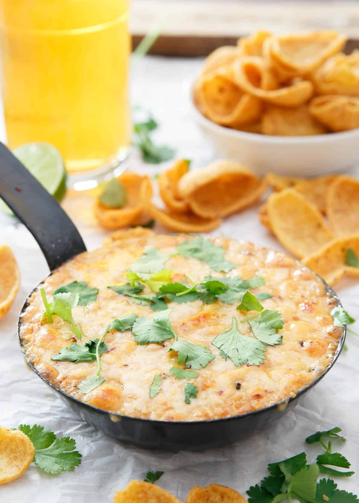This hummus fundido has a spicy chipotle kick to it. Use chips or even roasted vegetables to dive into this baked cheesy dip.