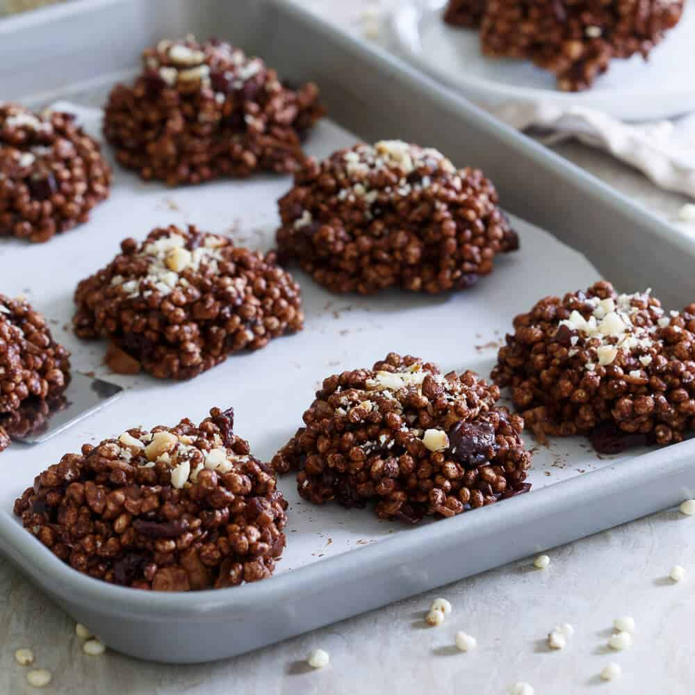 These puffed millet cookies are a no bake treat coated in dark chocolate and filled with dried cranberries and toasted macadamia nuts.