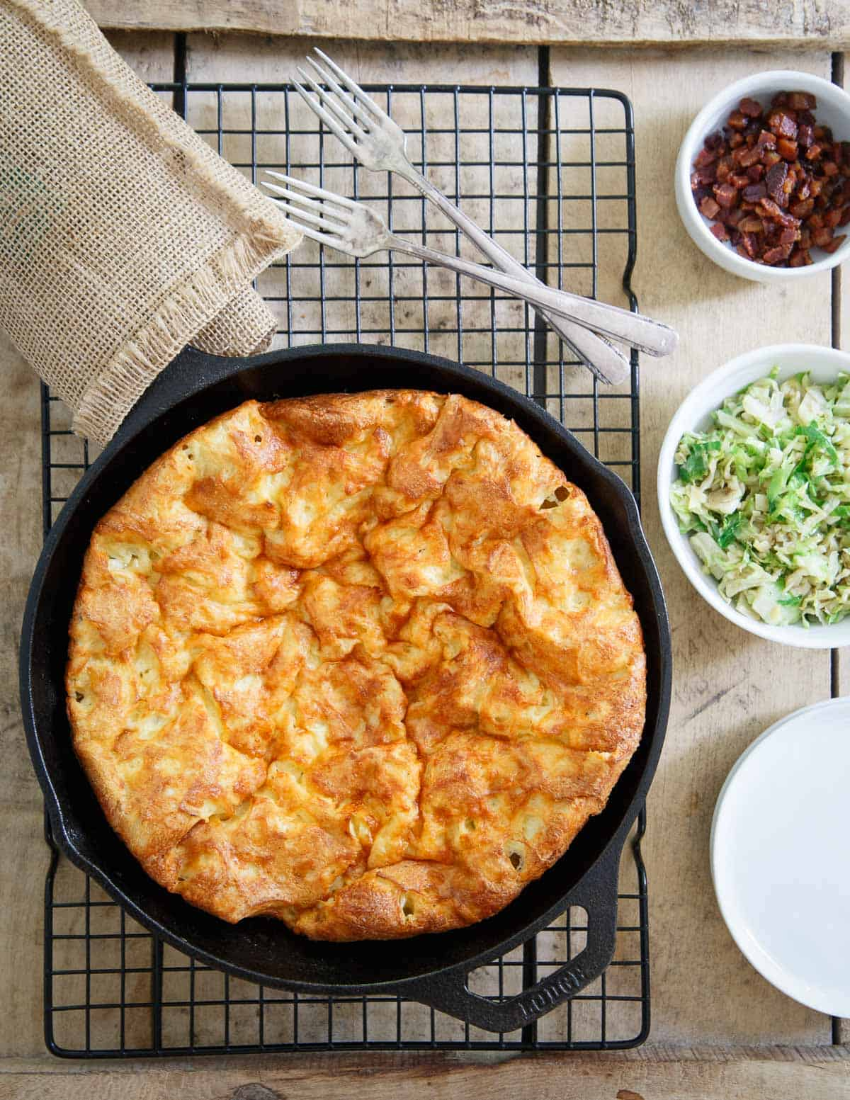 A savory Cheddar Dutch Baby gets topped with bacon and brussels for an easy dinner or brunch.