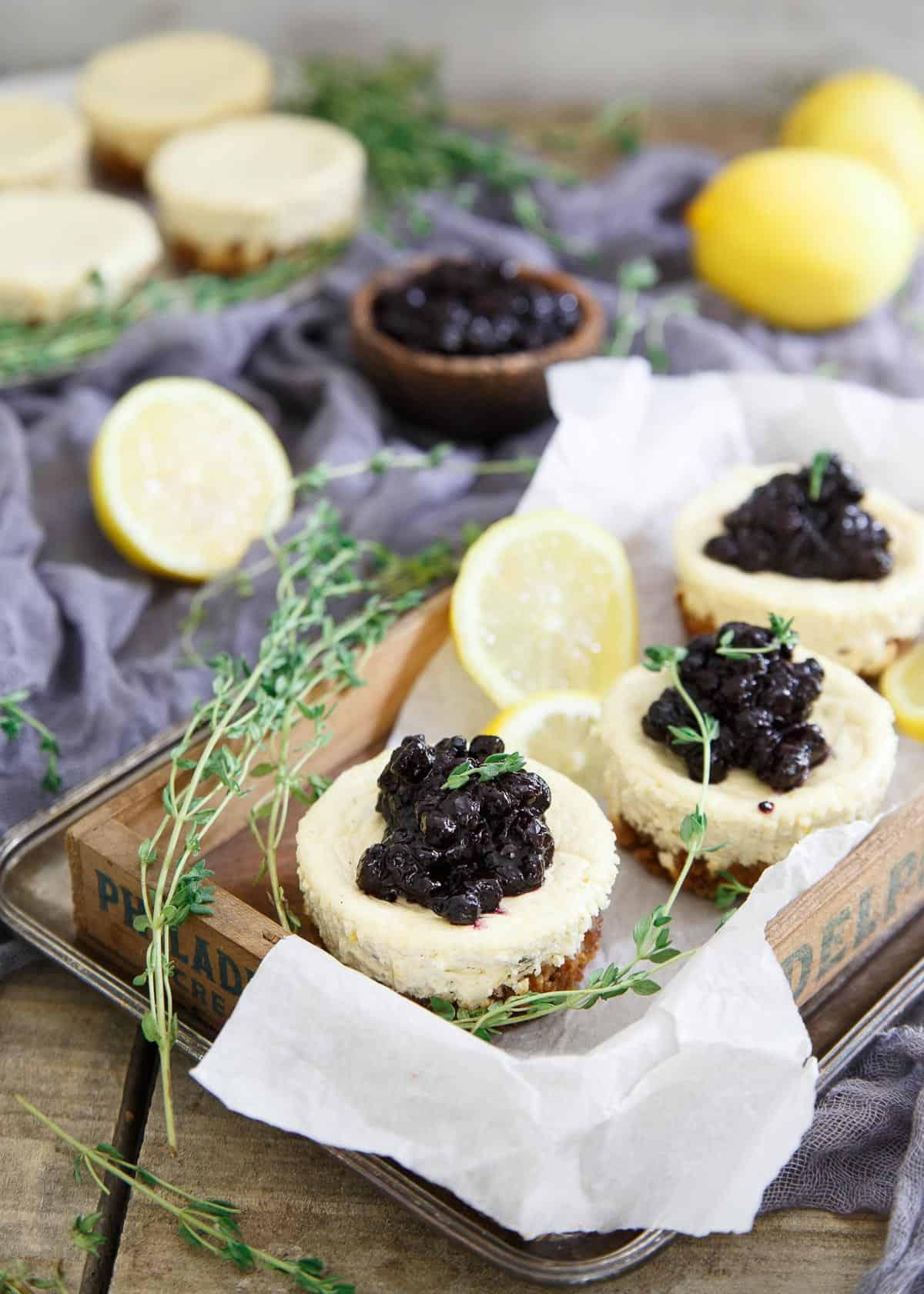 These gluten free granola crust mini cheesecakes are infused with lemon and thyme and topped with a quick blueberry thyme compote.