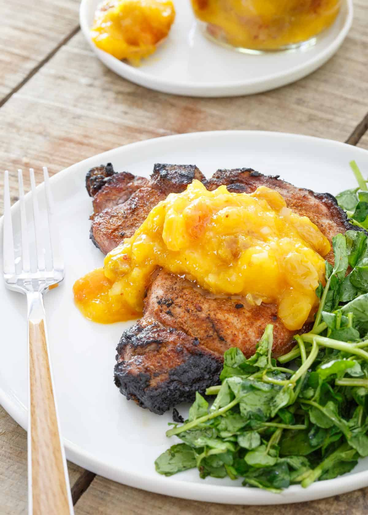 Spice Rubbed Pork Chops are topped with Mango Peach Chutney for a sweet and spicy bite.