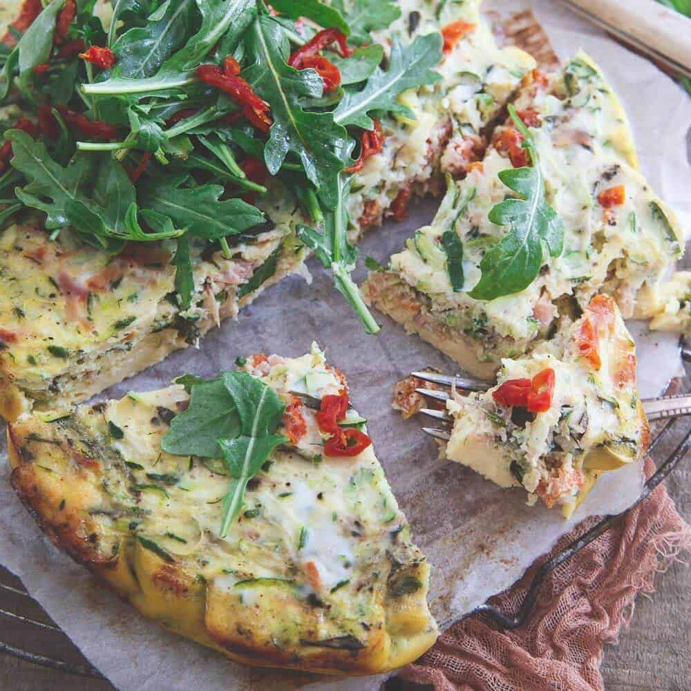 This slow cooker frittata is bursting with grated zucchini, sun dried tomatoes, basil and prosciutto then topped with a simple arugula salad. Great for a summer breakfast or dinner!
