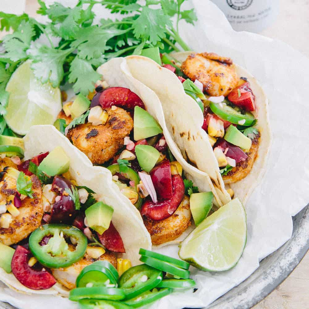 With a simple salsa full of juicy cherries, grilled corn and spicy jalapeños, these blackened shrimp tacos are a great summer meal.