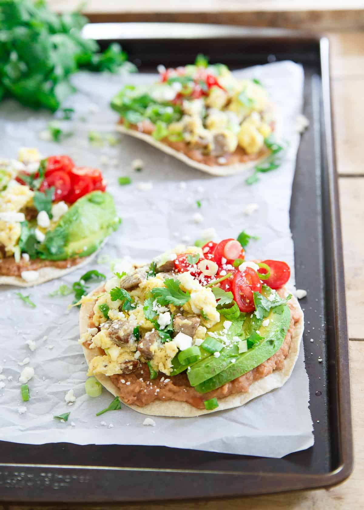 These breakfast tostadas include chicken sausage scrambled eggs piled high on a refried bean base. Avocado, tomatoes and cotija top it all off!