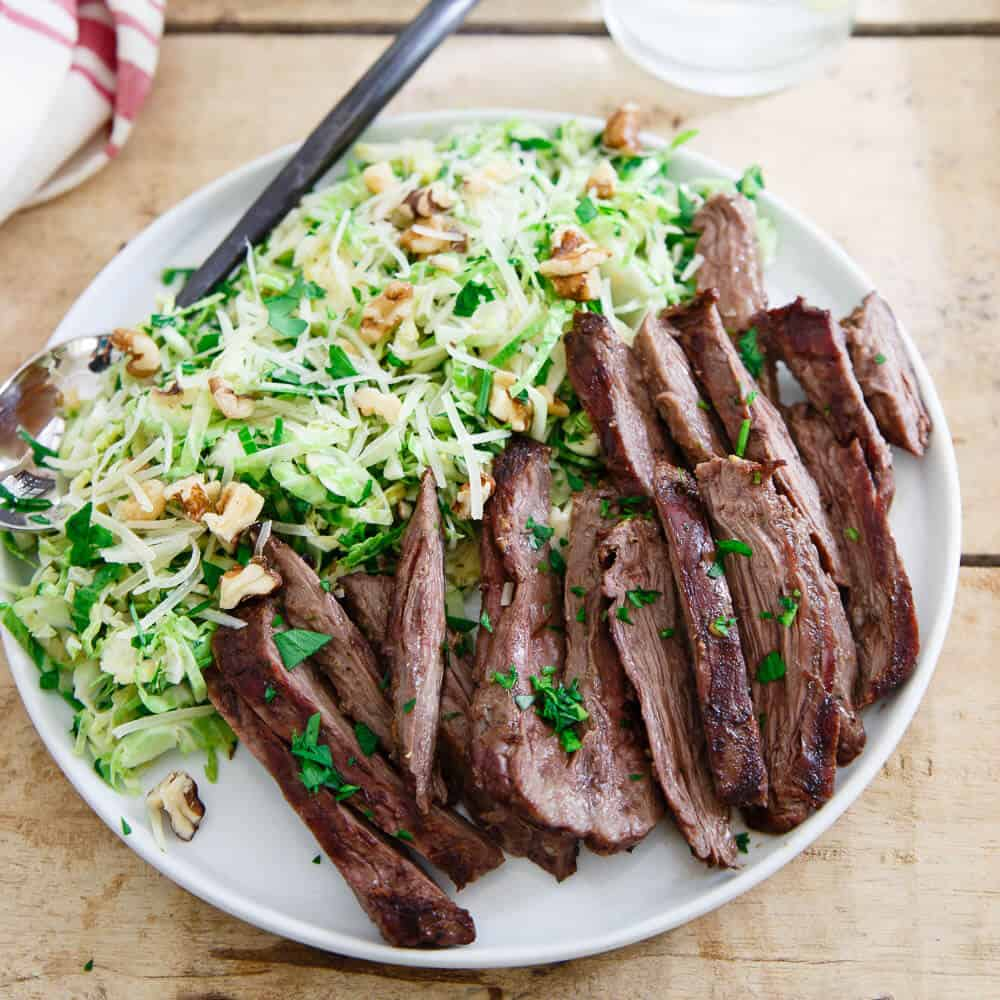 This grilled skirt steak is the perfect summer meal served with a chopped brussels sprouts salad tossed in a lemon dijon dressing.