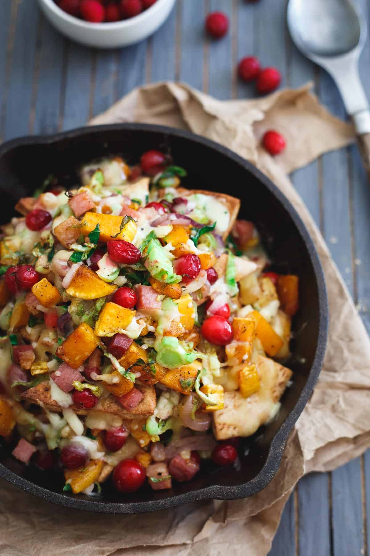 These butternut squash pita nachos bring a fall twist to the table packed with brussels sprouts, cranberries, pancetta and caramelized onions.