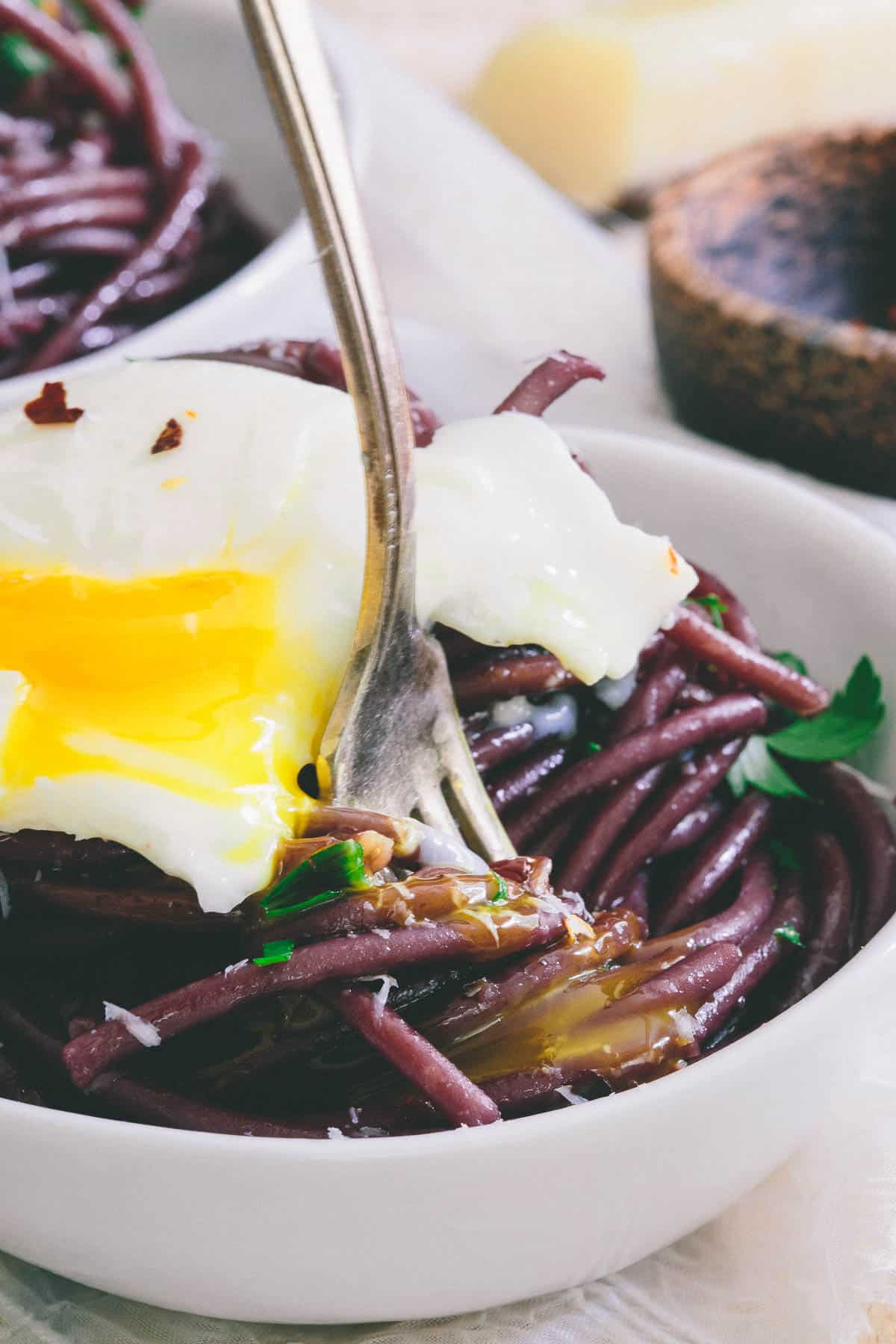 Cooking the pasta in red wine gives this bucatini it's gorgeous color. Top with a soft boiled egg for an easy meal!