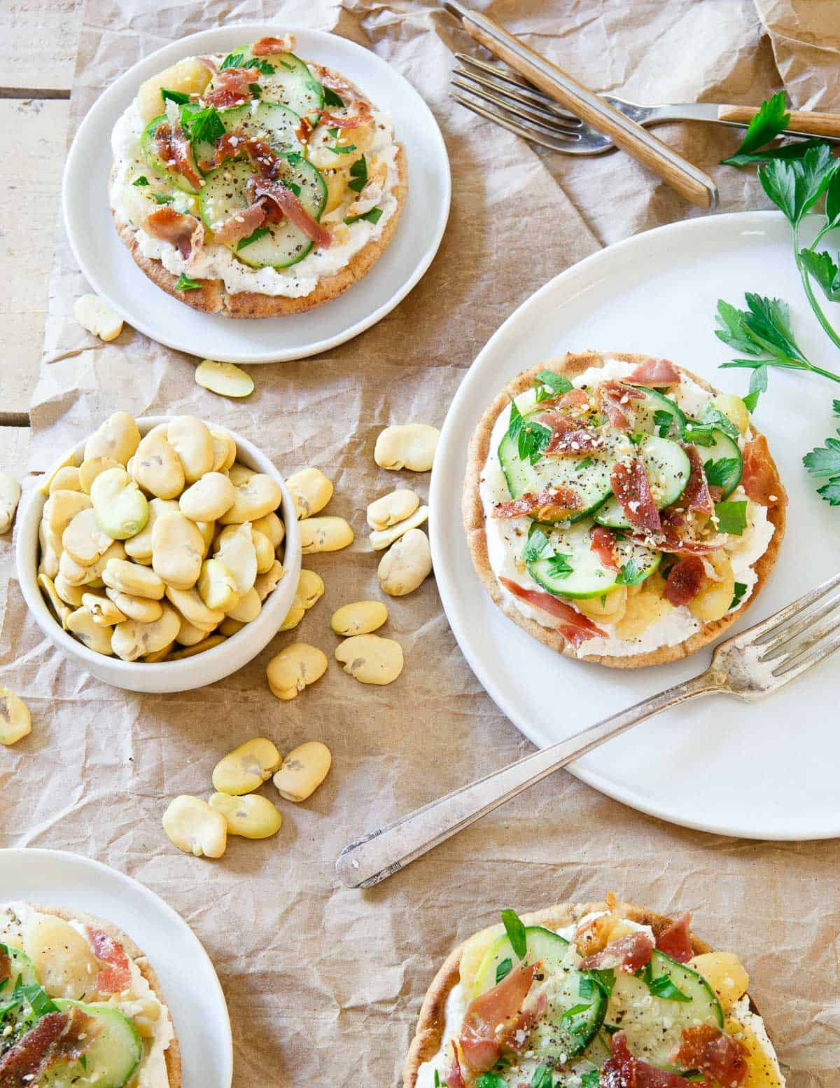These fava bean grilled pita bites are layered with a base of creamy ricotta, tangy pickled cucumbers and crisp salty prosciutto. They make a sensational bite for a light lunch or appetizer!