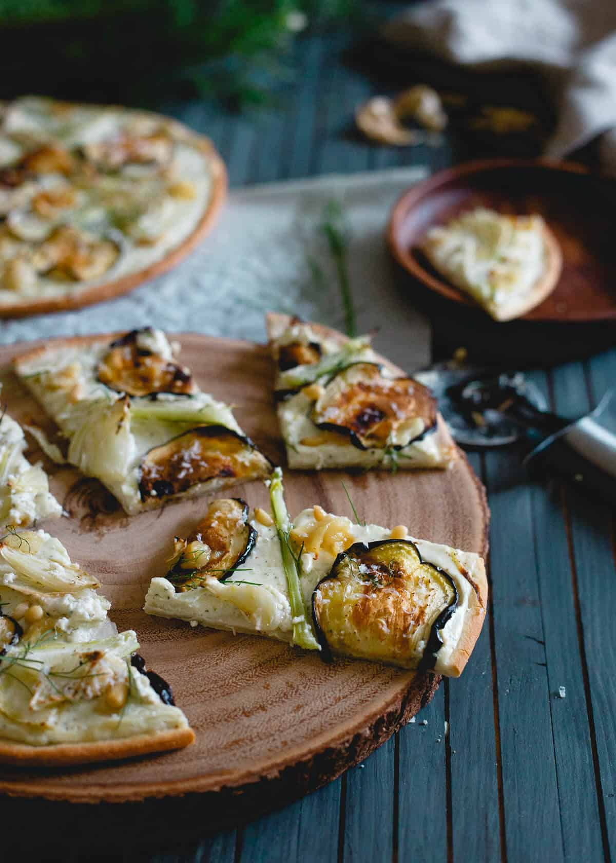 If you love white pizza, you'll love this roasted eggplant fennel pizza! It has a whipped feta and ricotta base with toasted pine nuts, creamy roasted garlic cloves and an olive oil drizzle to top it off.