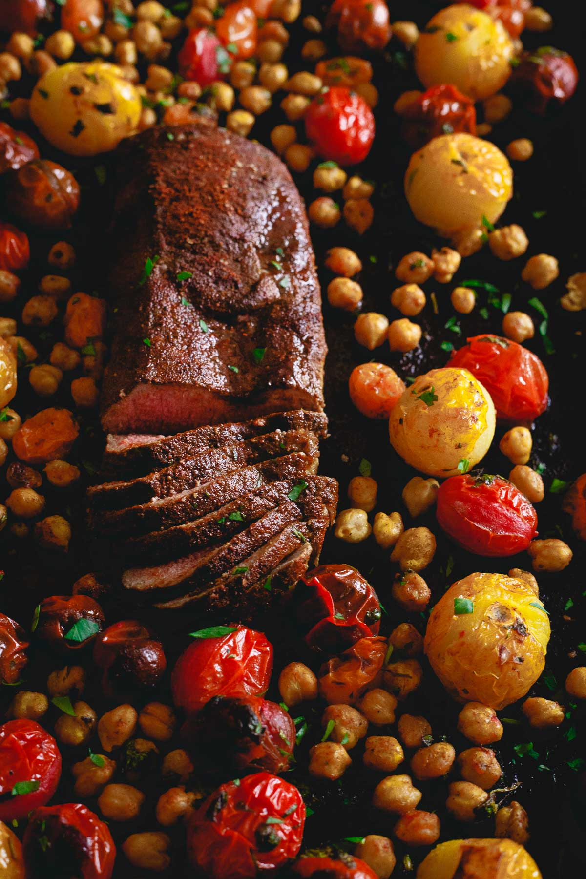 Get dinner on the table fast with this one pan roasted lamb dinner. Packed with flavorful spices, roasted tomatoes and chickpeas.