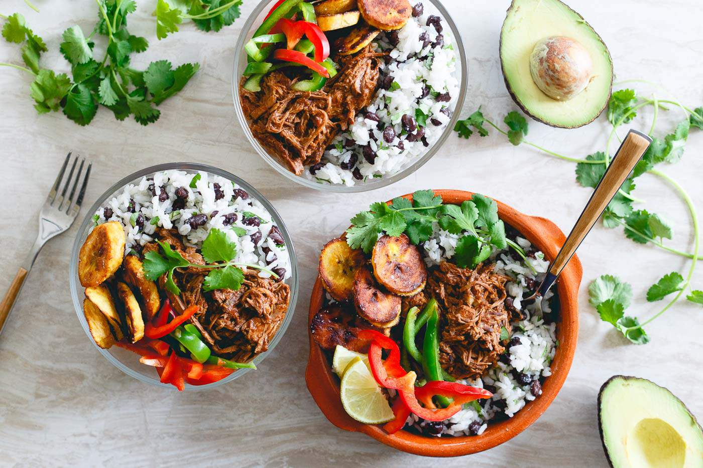 Pan-fried plantains, rice and beans and crispy peppers round out these slow cooker Mexican shredded beef bowls, the perfect meal prep idea for the week!