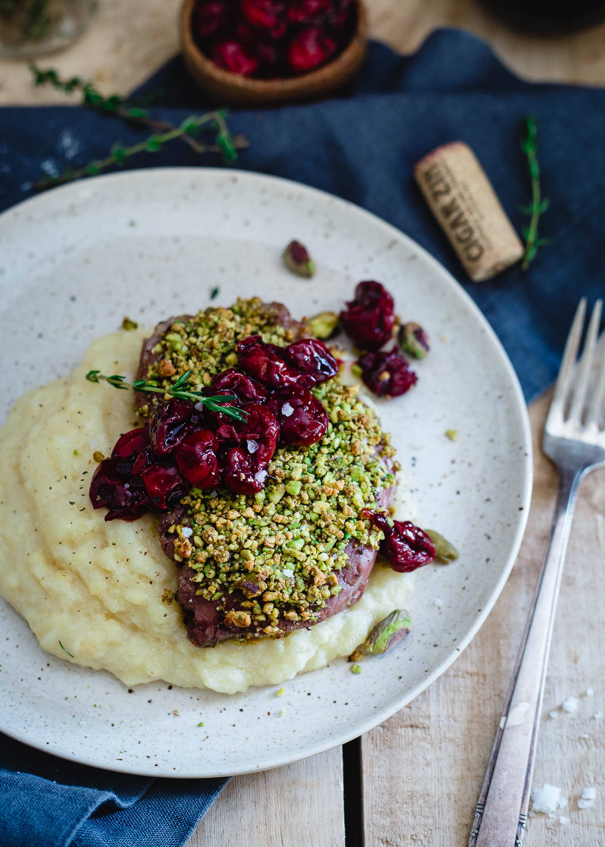 Pistachio crusted lamb chops are topped with a simple red wine cherry sauce and served over creamy parmesan polenta. It's fancy food made simple and perfect for a special Valentine's Day dinner.