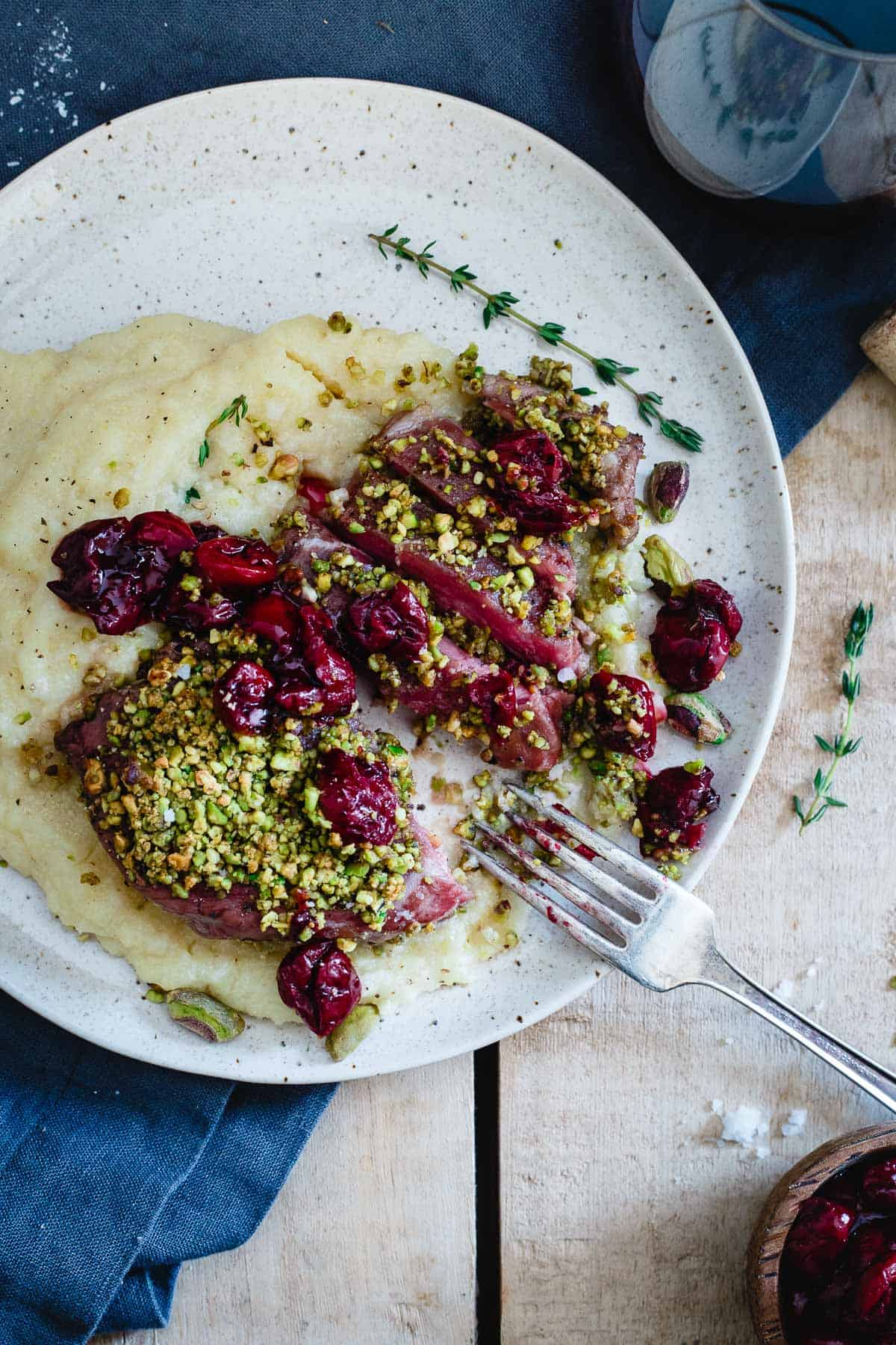 Red wine cherries and creamy parmesan polenta take these pistachio crusted lamb chops to the next level!