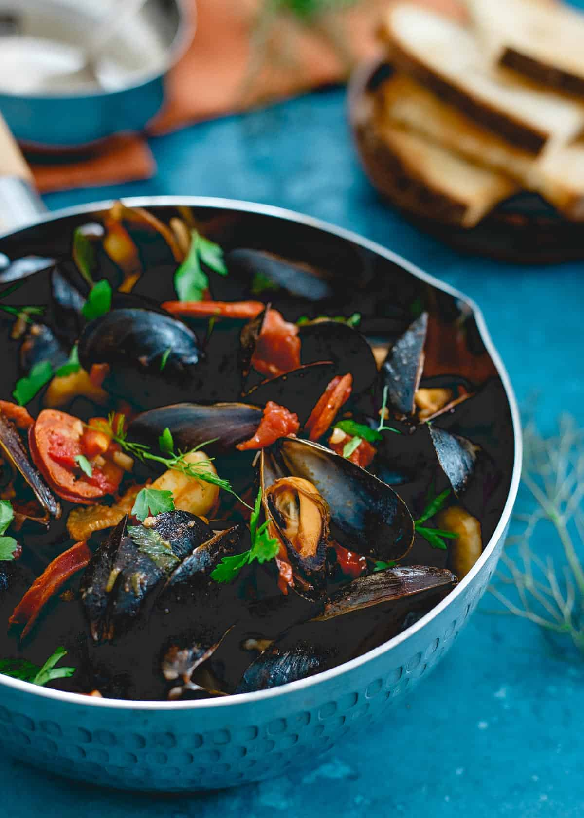 These spicy chorizo mussels are an easy, one pot meal made in 20 minutes with spicy dried chiles, fennel and chorizo in a chunky tomato broth. Serve with some warm crusty bread for a seafood feast!