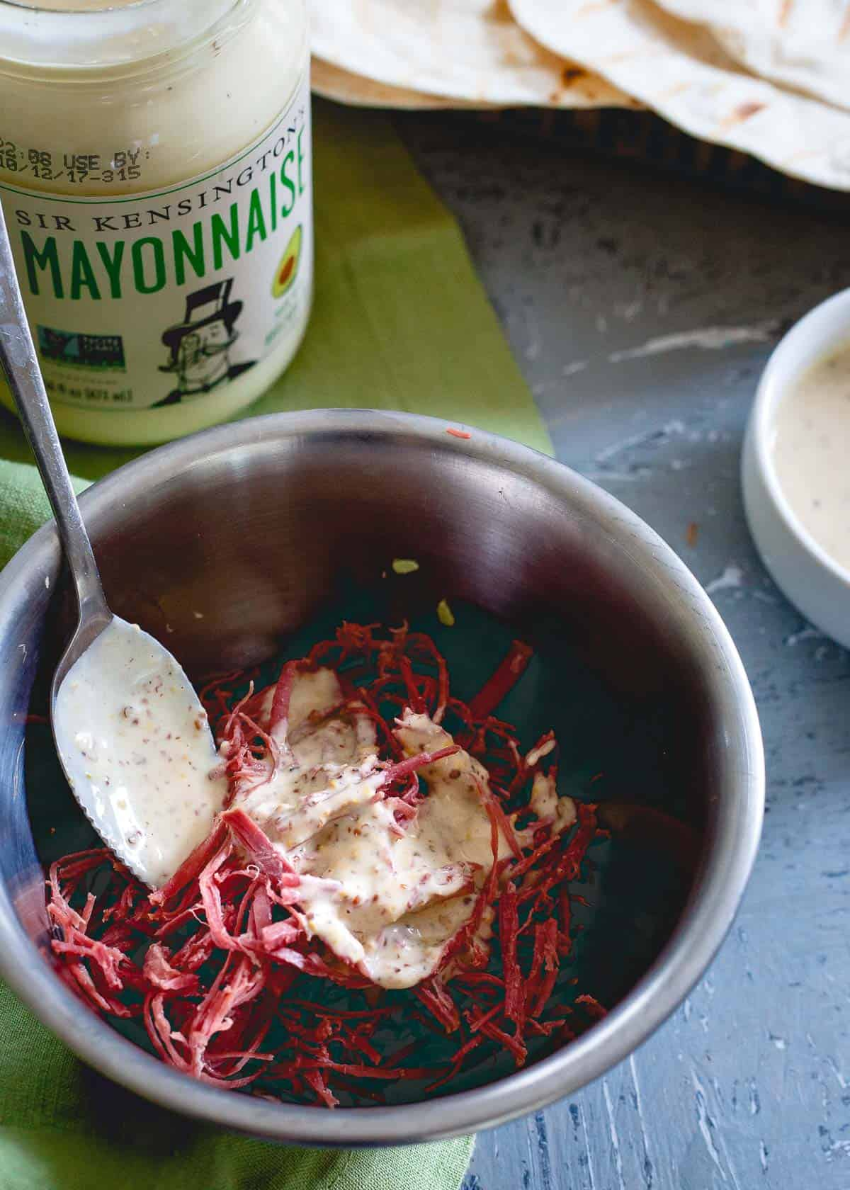 Avocado mayonnaise is used to make a creamy spicy mustard sauce in these corned beef tacos.