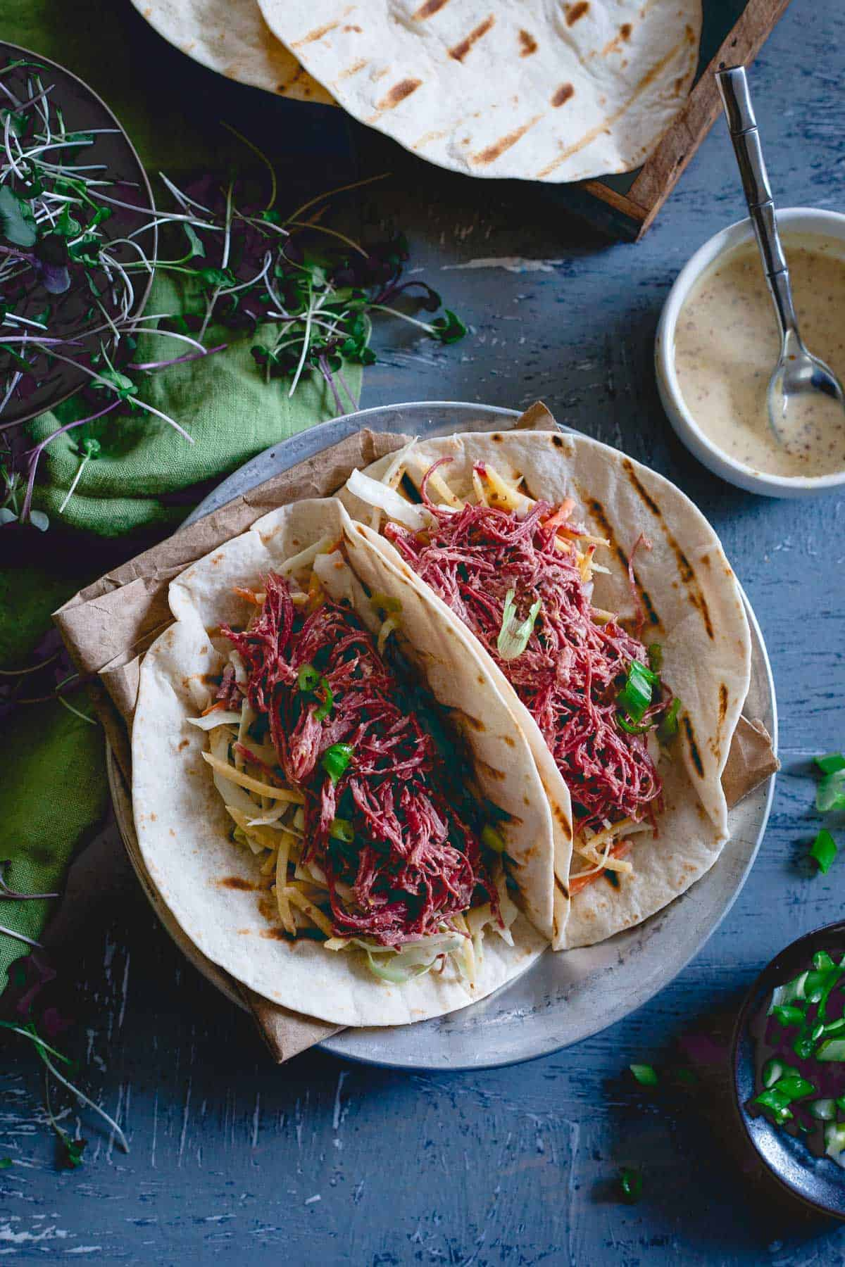 Corned beef tacos are served with a carrot cabbage slaw both tossed in a creamy spicy mustard sauce.