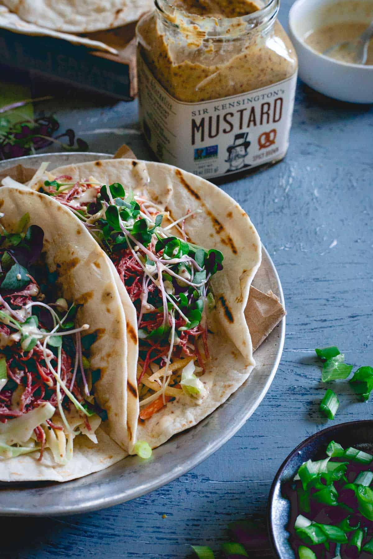 These corned beef tacos are served with a creamy spicy mustard sauce, a simple cabbage carrot slaw and topped with microgreens. Celebrate St. Patrick's Day with a Mexican twist!