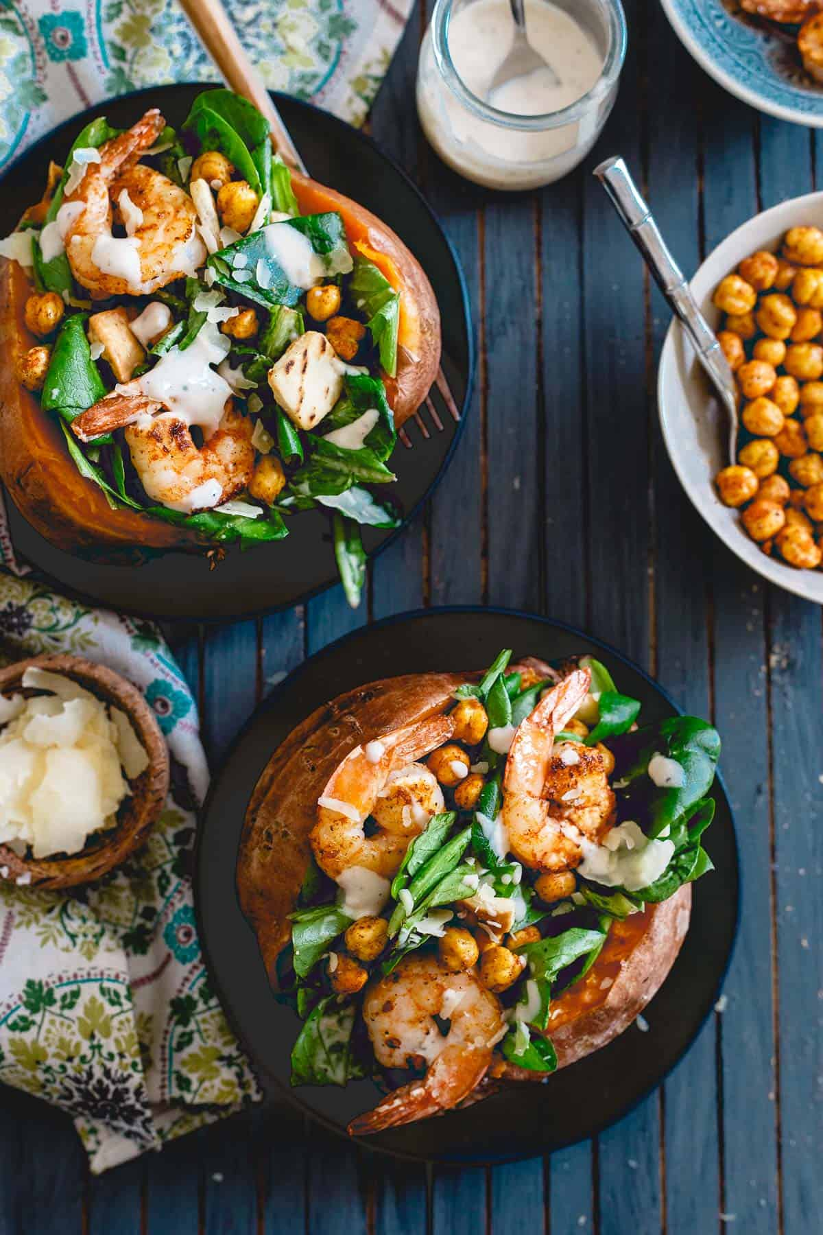 Spicy shrimp and roasted chickpeas add a bunch of flavor and satiety to these caesar salad stuffed sweet potatoes.