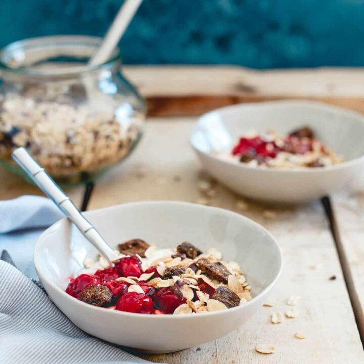 These breakfast yogurt bowls are topped with a tart cherry ginger muesli. Loaded with oats, almonds, cacao nibs, ginger, dried tart cherries and warm spices. With a swirl of cherry sauce, it's a tasty and nutritious way to start the day.