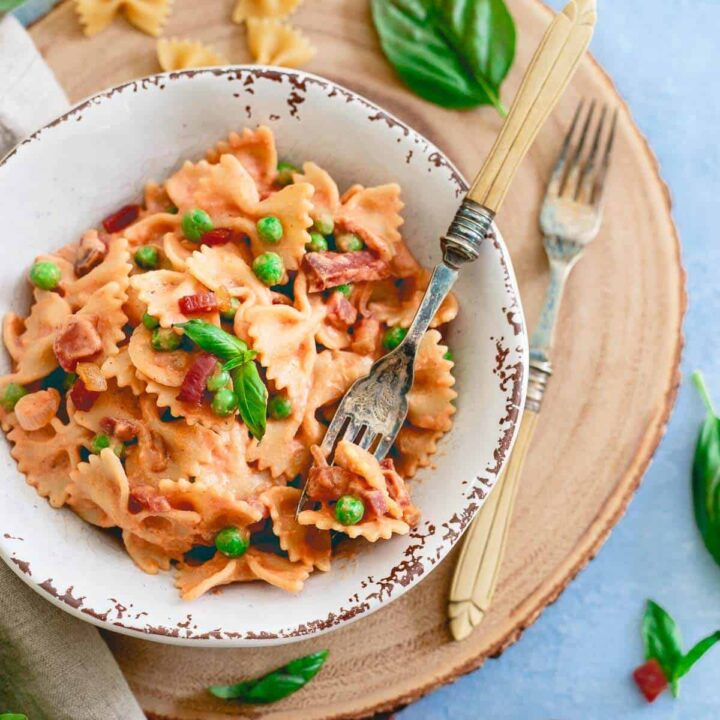 This 20 minute creamy tomato farfalle brings a healthy takeon traditional cream sauce with peas and crispy prosciutto for an easy, filling meal.