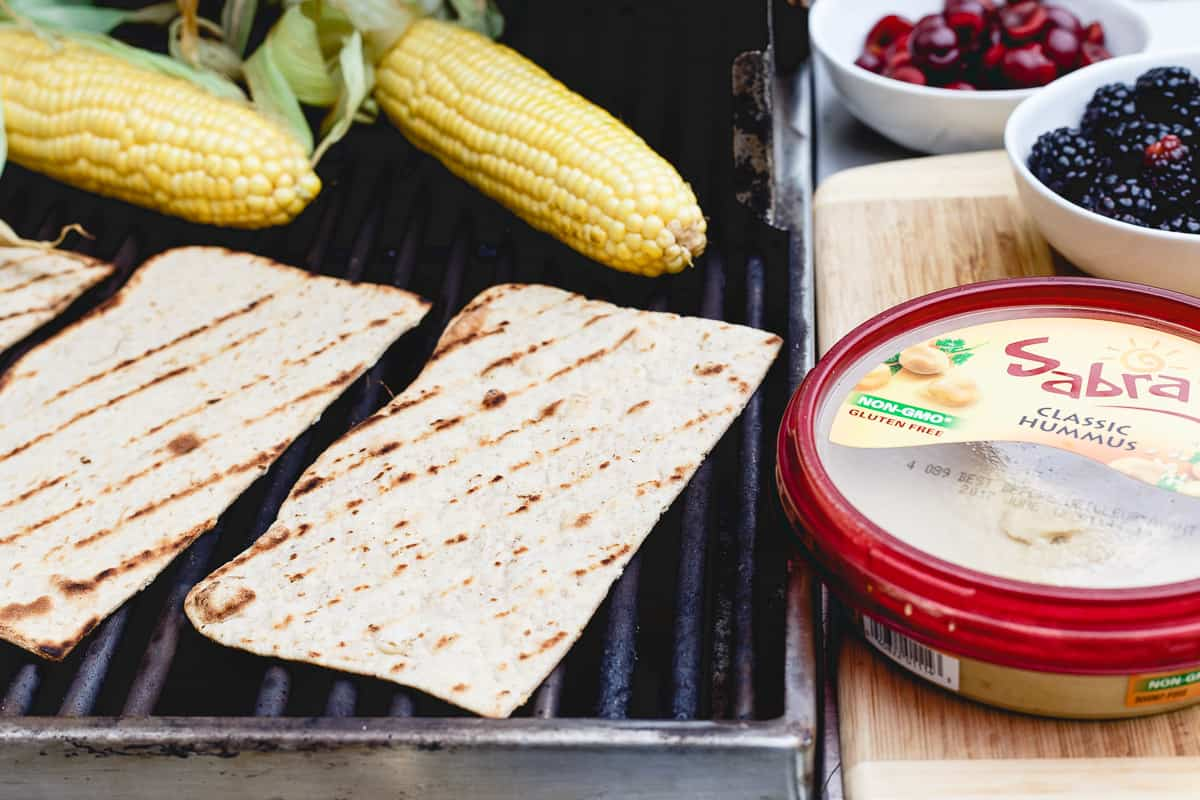 Grilled corn, berries, fresh cherries and hummus make a delicious flatbread for summer dining.