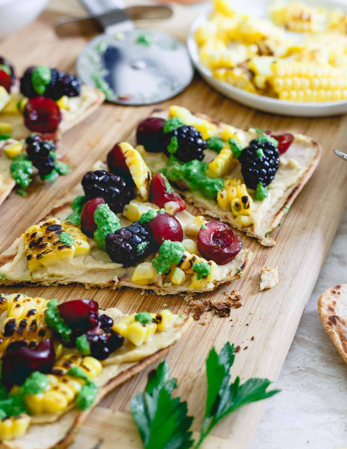 This summer inspired hummus flatbread is topped with grilled corn, berries and drizzled with a fresh roasted garlic parsley pesto. A great pre-dinner bite!