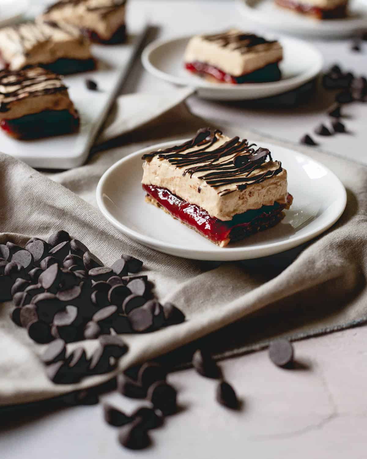 These peanut butter and jelly frozen yogurt bars have a chewy granola bar base and layers of sweet strawberry jelly, creamy peanut butter yogurt and a chocolate drizzle topping.