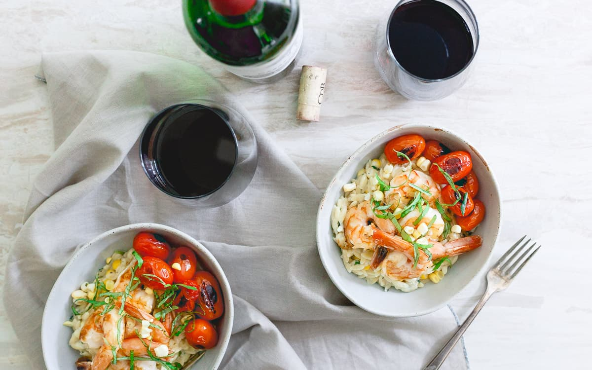 A bed of creamy parmesan orzo with summer corn and basil is topped with simple brown butter shrimp for an easy, elegant summer meal.